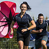 Sports students running with parachutes