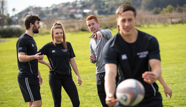 Students reviewing athlete passing a rugby ball